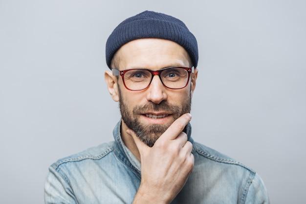 自信を持って満足しているひげを生やした男性はあごに手をつないで、会話を注意深く聞き、ファッショナブルな服を着ています