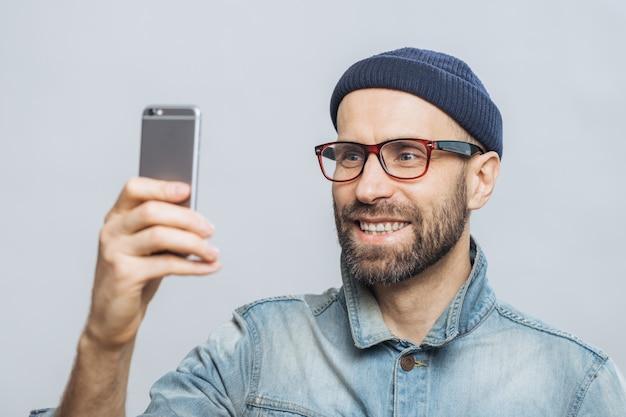 幸せな中年の笑みを浮かべて男性の肖像画は、デニムジャケット、帽子、メガネを着ています。