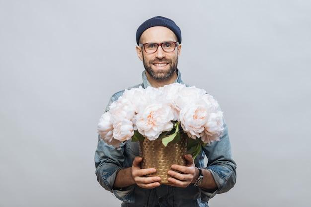 ポジティブなひげを剃っていない男性は眼鏡をかけ、花の美しい花束を保持します
