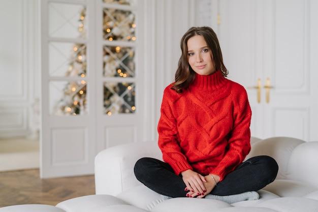 Женщина, одетая в теплый красный вязаный свитер, сидит скрещенные ноги в позе лотоса на диване.