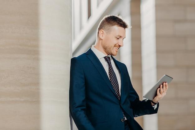 フォーマルなスーツでエレガントなビジネスマン、手でデジタルタブレットを保持