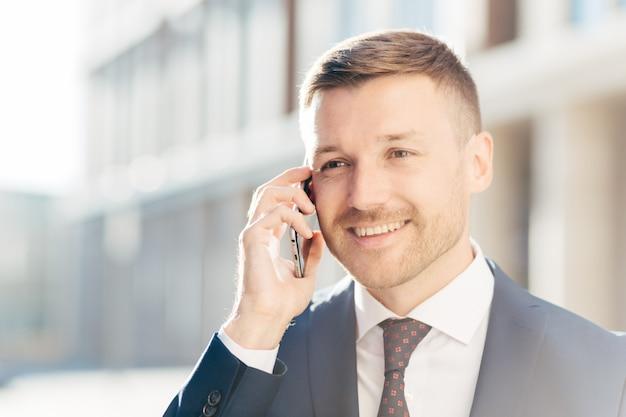 自信を持って幸せな中年のビジネスマンは携帯電話で通信します