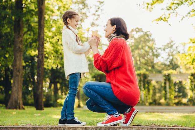 暖かいニットの赤いセーターの若い母親は公園で彼女の小さな娘と遊ぶ、彼女の葉を与える、晴れた秋の天気を楽しむ