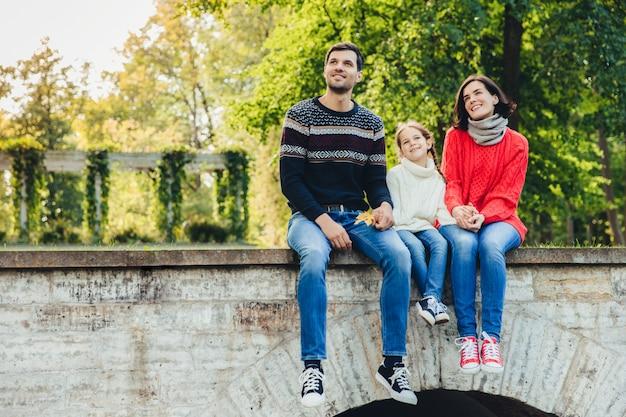 愛らしい子供の横の肖像画は、彼女の母と父の間に座って、美しい風景を楽しみます