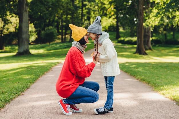 Мать и дочь держат носы близко друг к другу, наслаждаются спокойной атмосферой