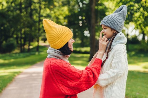 喜んで女性はトレンディな黄色の帽子を着て、小さな娘の鼻に触れるスカーフと赤いセーター