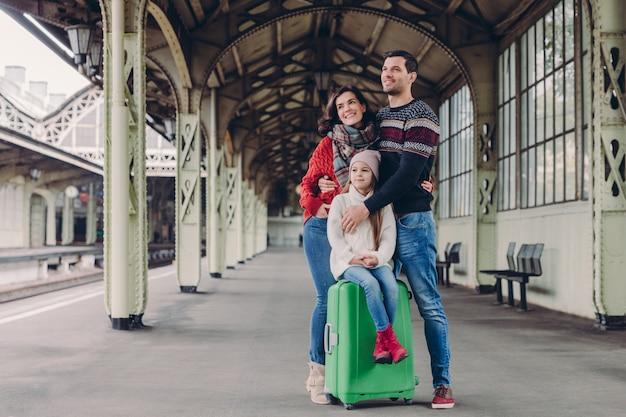 Жена и муж обнимаются с любовью, дочь сидит у чемодана, вместе позирует на платформе.