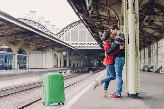 Прекрасный парень и девушка стоят рядом, обнимаются и целуются, ждут транспорта на вокзале