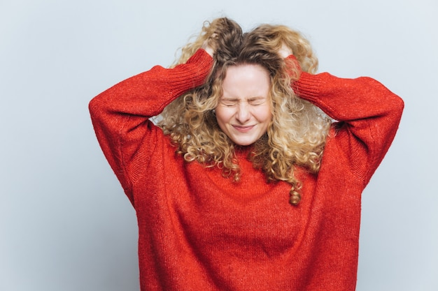 Напряженная разочарованная белокурая женщина вырывает волосы, сожалеет, что сделала неправильно
