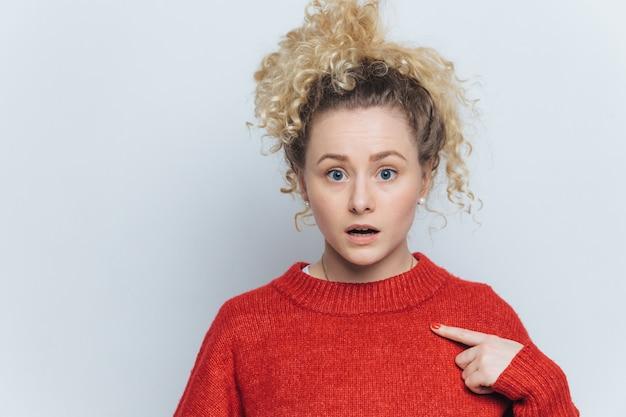 Потрясенная ошеломленная молодая женщина с удивленным выражением лица указывает на пустой красный свитер