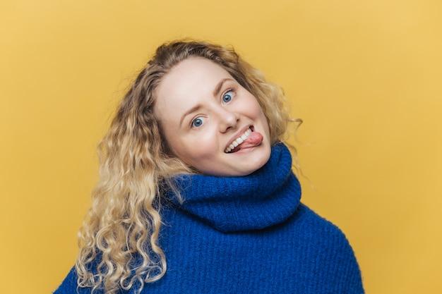 肯定的な表情で面白い漫画巻き毛の若い女性は、舌を示し、友人と楽しんでいます