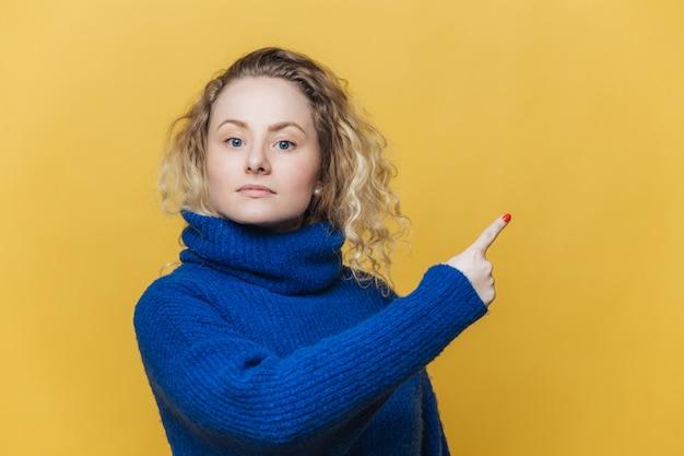 Серьезная блондинка молодая женщина с вьющимися светлыми волосами, одетая в ярко-синий свитер, указывает на пустую копию пространства