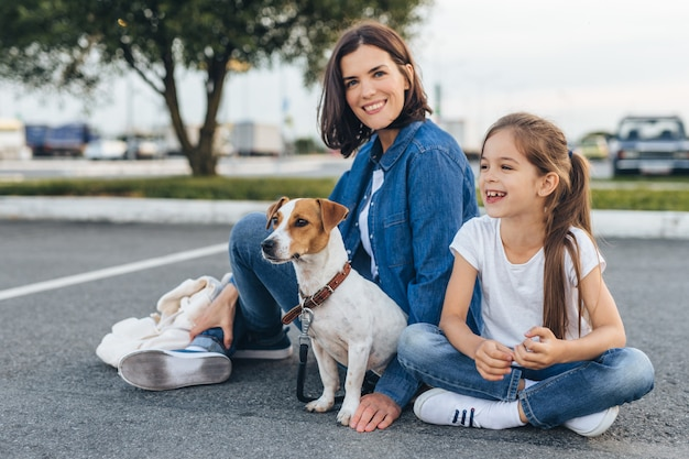 Счастливая мама с девочкой и собакой
