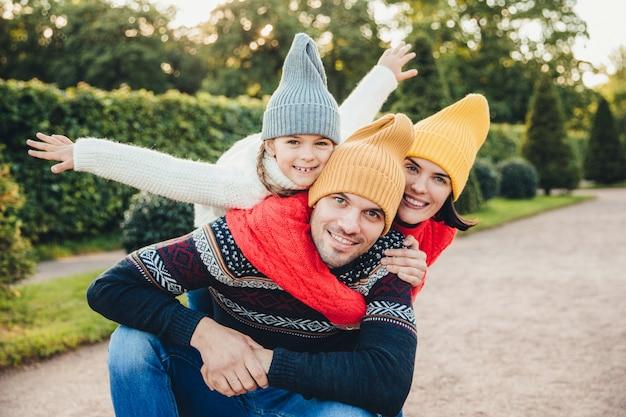 Приятно провести время вместе! улыбающиеся возбужденные женщина, мужчина и их маленькая девочка, носят теплую вязаную одежду