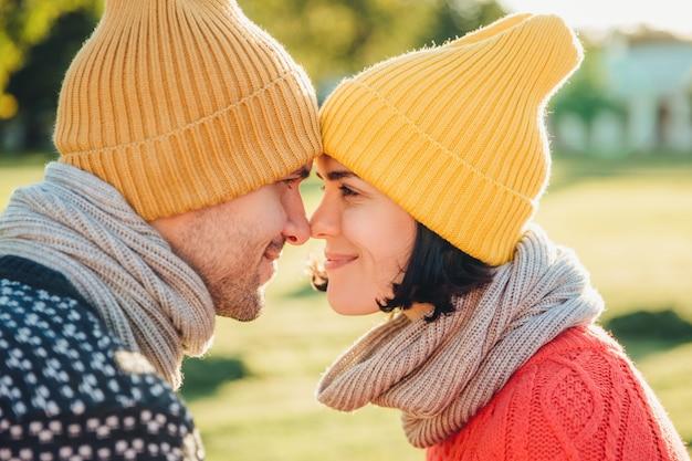 素敵なカップルのポートレートを閉じます暖かい帽子を着て、幸せと楽しさに満ちた目でスカーフを見て