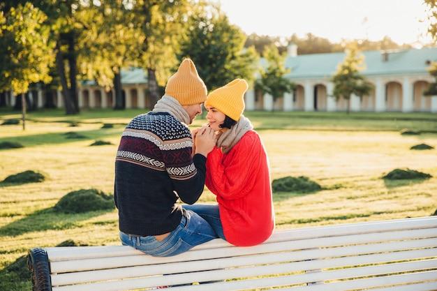 ロマンチックなカップルはベンチに座って、晴れた日を楽しみ、手をつないで、お互いに大きな愛をもって見ます