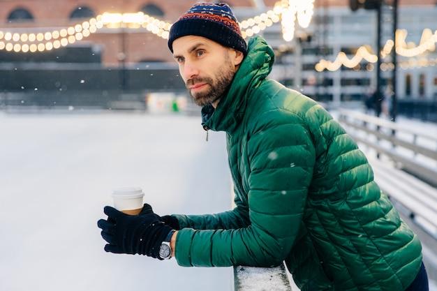 Задумчивый мужчина с густой бородой опирается на него, держит на вынос кофе, смотрит на хоккейный матч зимой