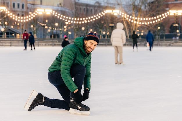 Человек в зеленом пальто, зашнурует коньки, радостно смотрит в камеру, стоит на чудесном ледяном кольце
