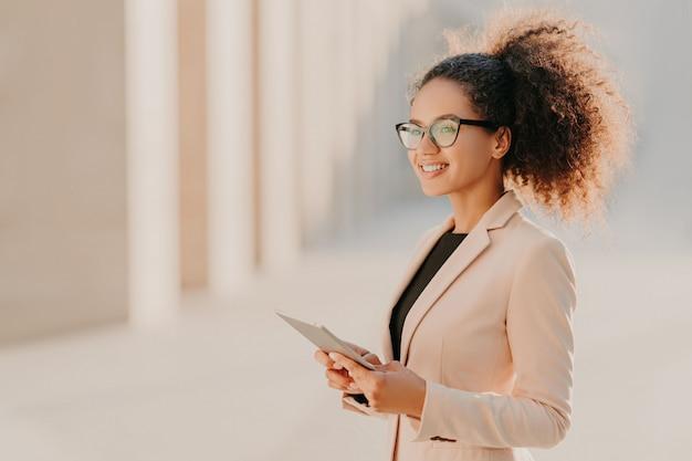 エレガントな服を着てアフロの髪の黒い肌の女性を喜んで手でタブレットコンピューターを保持