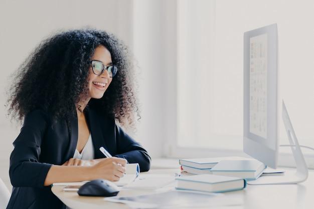 縮れ毛の女性マネージャーがレポートを作成し、画面に焦点を合わせ、情報を書き留め、メガネとフォーマルなスーツを着ています