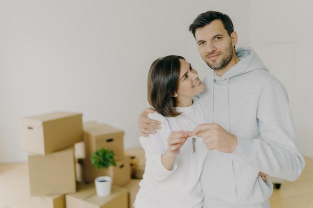 Счастливая пара обнимаются в пустой комнате, держат ключи, только что приехали в собственную квартиру