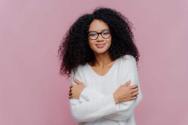 気持ちの良いミレニアル世代のアフロ女性は、手を胸の上で交差させ、毛むくじゃらの毛をまとい、白い快適なセーターと眼鏡を着ています。