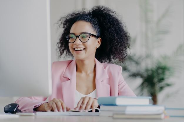 Рад, что кудрявая профессиональная женщина-менеджер сосредоточена на экране компьютера, широко улыбается, имеет вьющиеся волосы, носит прозрачные очки, элегантный костюм, позирует на рабочем столе в своем кабинете, работает удаленно