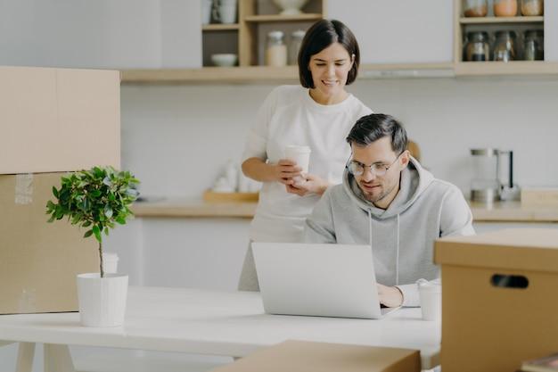 新婚カップルの写真は、新しく購入した家の家具について考え、現代のラップトップコンピューターでインターネットでいくつかのアイデアを検索し、テイクアウトコーヒーを飲み、段ボール箱のあるモダンなキッチンでポーズをとる
