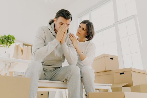 Фотография неудовлетворенного мужа и жены, вынужденных продать квартиру из-за финансовых проблем, женщина успокаивает мужа, позирует на картонных коробках, позирует в гостиной. переезд как вид стресса для семьи