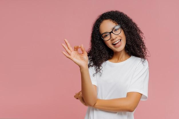 素敵な黒い肌の女性はいいジェスチャーをし、頭を傾け、承認を示し、何かに同意します