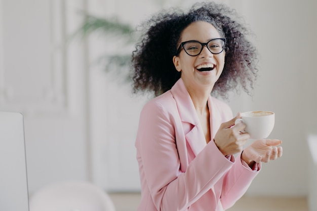 Обрадованная кудрявая женщина радостно смеется, в то время как пьет горячий кофе