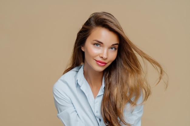 Привлекательная молодая женщина имеет светлые волосы, плавающие в ветер