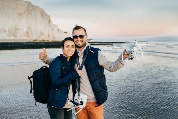 幸せな女性と男性の旅行者は、バッグと、彼らが見るものの写真とビデオを作成するための最新の技術を持っています