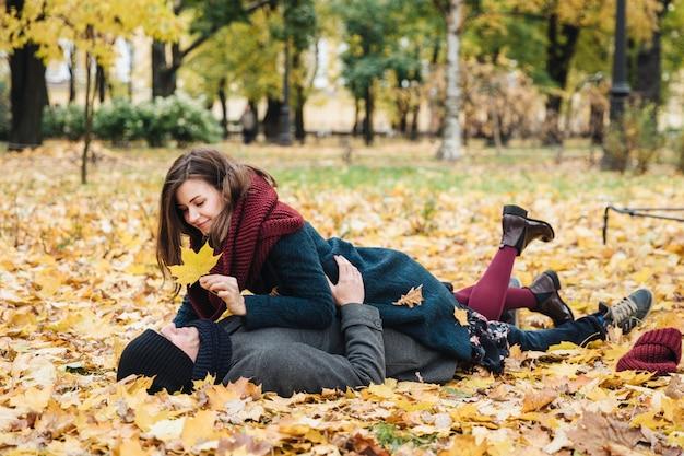 愛のカップルは一緒に楽しんで、黄色の葉で覆われた地面に横たわって、お互いを見て、愚か者を演じます