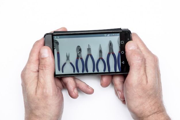 男性の携帯電話を保持しています。画面上のツールの写真。