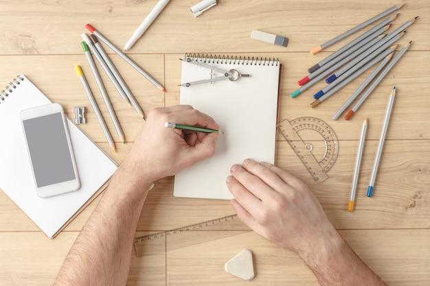 デザイナーは木製のテーブルの上のノートにスケッチを描きます。文房具。上からの眺め。