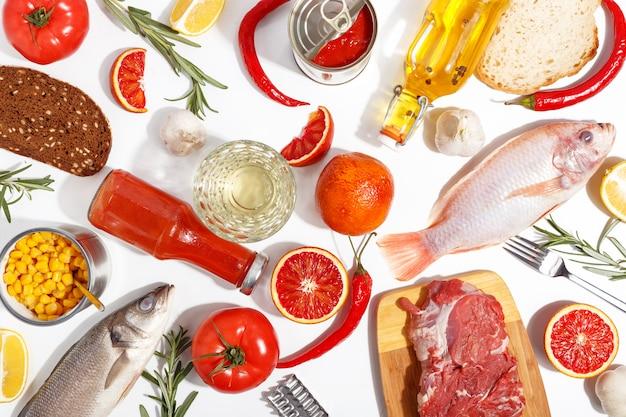 健康食品きれいな食事の選択:果物、野菜、種子、魚、肉、白い背景の上の葉の野菜。上面図。
