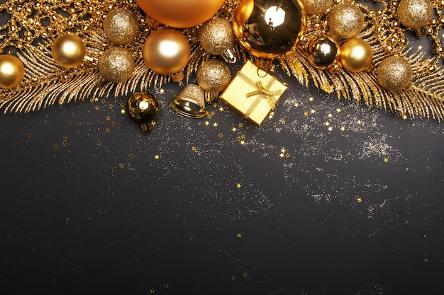 黄金のクリスマスのおもちゃと黒の背景に装飾要素のクリスマス組成。