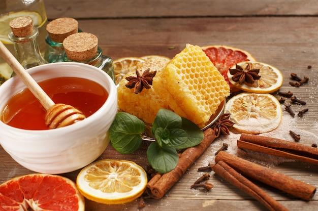 Мед, корица и сухофрукты на деревянном столе. здоровое питание.