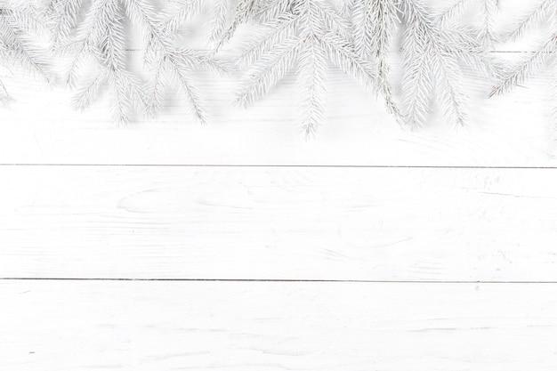クリスマスの組成物。白い木製の背景にモミの枝で作られたフレーム