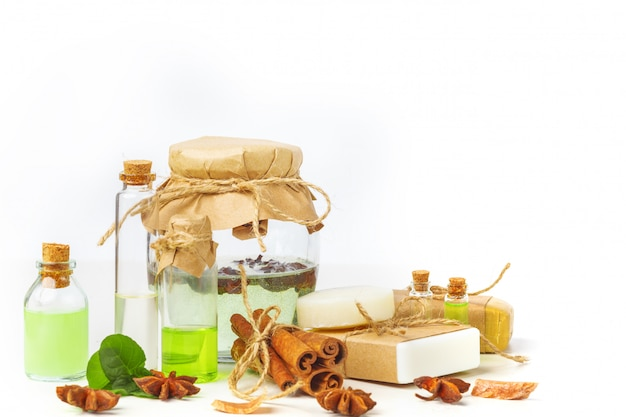 Ароматические масла в стеклянных бутылках на белом столе. уход за телом. здоровый образ жизни. изолированные.