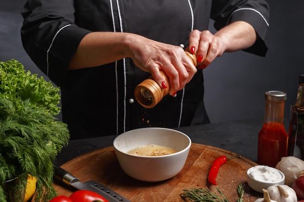 Девушка повар в черной униформе готовит еду.
