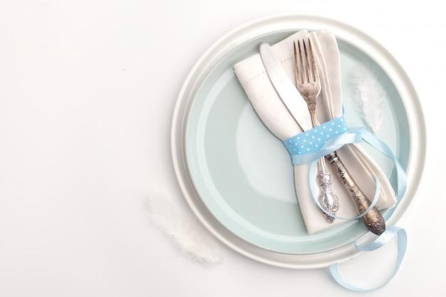 Элегантная стильная сервировка стола. нож и вилка на салфетке на тарелку на белой поверхности.