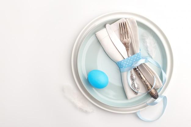 エレガントでスタイリッシュなテーブルセッティング。白い表面の皿の上のナプキンにナイフとフォーク。