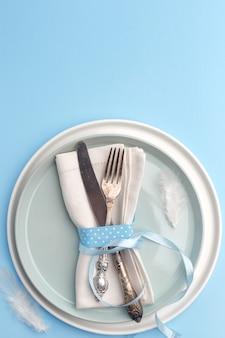 エレガントでスタイリッシュなテーブルセッティング。ナイフとフォークを青い表面の皿の上のナプキンに。