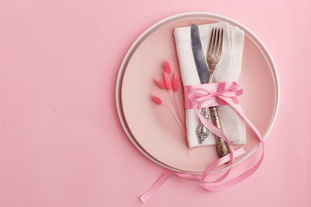 エレガントでスタイリッシュなテーブルセッティング。ピンクの表面の皿の上のナプキンにナイフとフォーク。