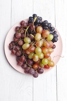 白い木の皿に熟したジューシーなブドウ。上面図。
