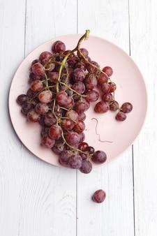 Спелый сочный виноград на тарелку на белой древесине. вид сверху.