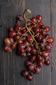木製のテーブルに熟したブドウの房。上面図。