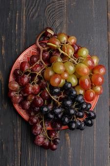 暗い木の皿に熟したジューシーなブドウ。上面図。